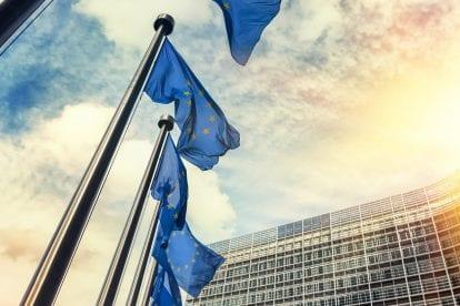 Wehende Fahnen vorm EU-Parlament im Sonnenuntergang