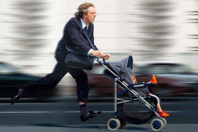 Foto eines Vaters mit Kinderwagen in Hektik