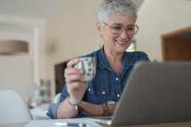portrait of a 55 year old senior woman working on her laptop in her home